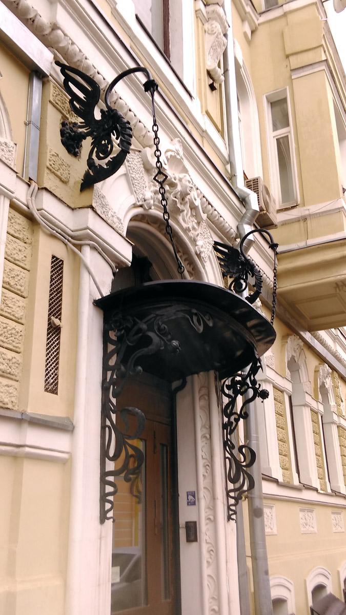 Нарядный металлический козырек над подъездом со стороны Армянского переулка, выполненный в стиле модерн, с двумя кронштейнами оригинального рисунка.