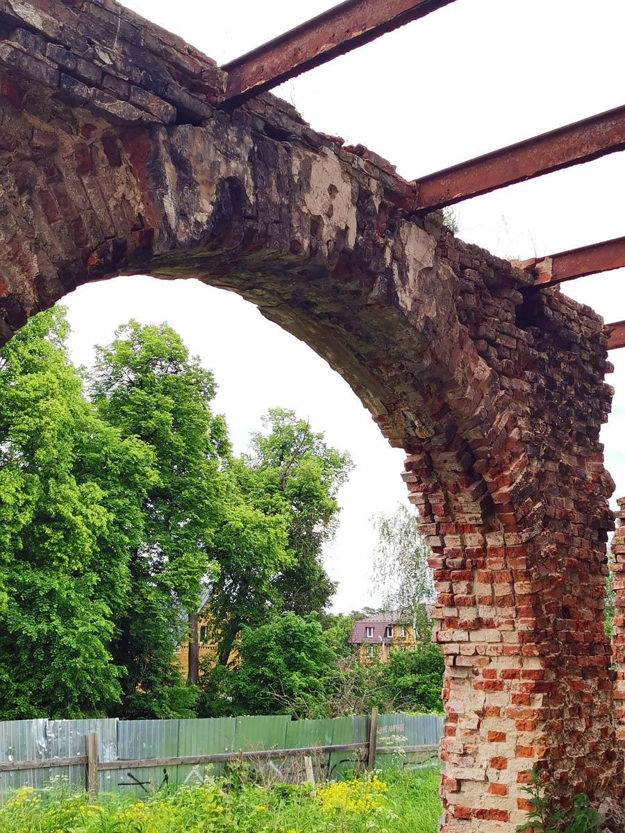 Романтичная руинированная арка и вековые липы усадебного парка за забором.