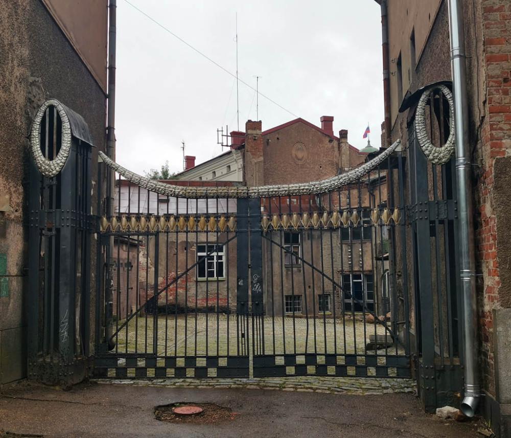 А между этими двумя зданиями расположены шикарные металлические ворота, выполненные так же в стиле модерн.