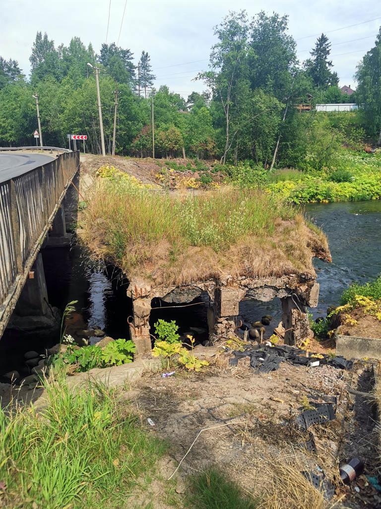 Рядом с храмом проходит автомобильная дорога через реку. Рядом с действующим мостом развалины старого моста