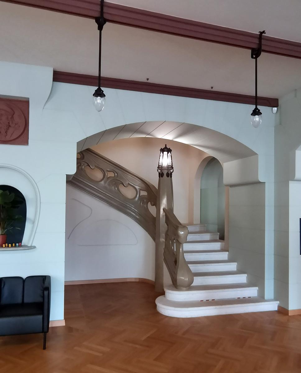 Парадная лестница на второй этаж. Выглядит, как застывшая лава или волна. По сути, она прообраз знаменитой лестницы в Особняке Ребушинских. Но есть принципиальное различие, в особняке лестница мраморная, а здесь гипсовая, покрашенная под мрамор.