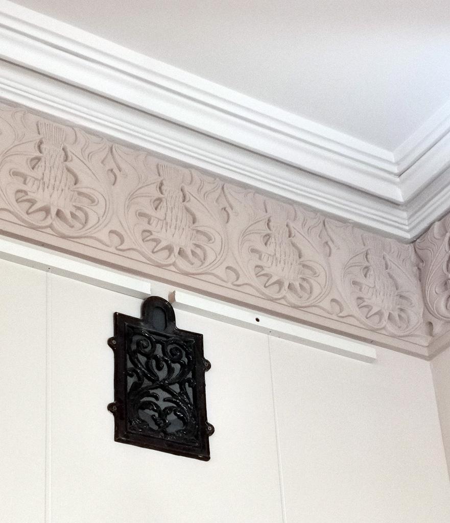 Потолочная лепнина в виде цветов чертополоха и вентиляционная решетка в комнате для совещаний.