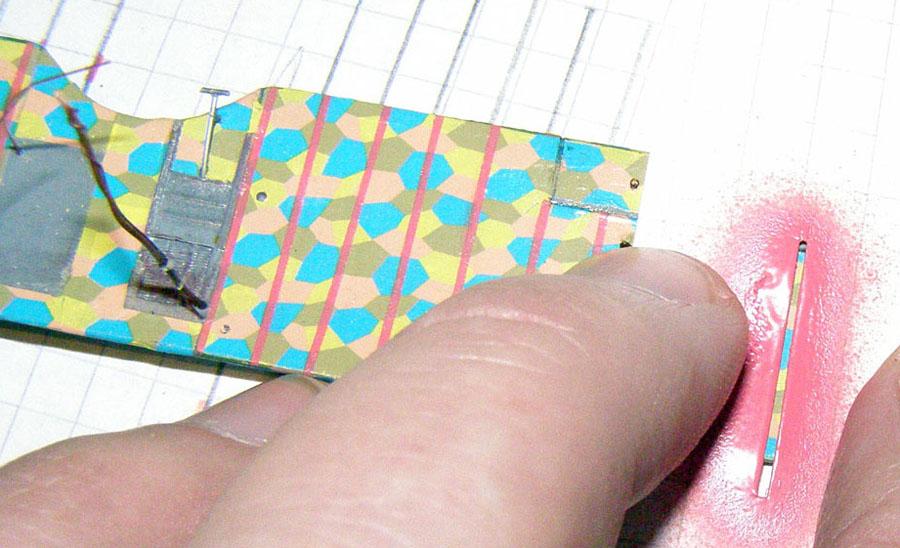 Вырезал скальпелем по линейке прорезь шириной примерно 0,7мм и длинной немного больше хорды крыльев. Приложил крыло на бумагу в клеточку и отметил расположения нервюр. Отложил крыло, прочертил параллельные полосы с запасом. Приложил крыло, совместил относительно полос, зафиксировал кусочками скоча по законцовкам крыла.Совместил прорезь трафарета с нервюрой. В этом помогают полосы под крылом. Далее трафарет можно было зафиксировать скотчем к листу бумаги, но я просто придержал рукой. Надул полосу аэрографом.