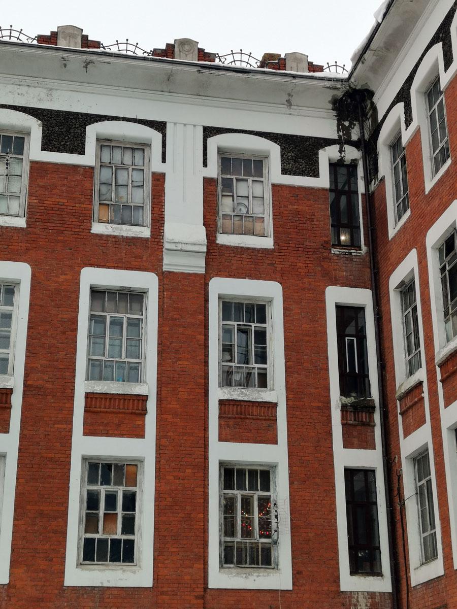 Видно, что с этой стороны здания часть комнат жилые, но большинство окон или разбито или заколочено...
