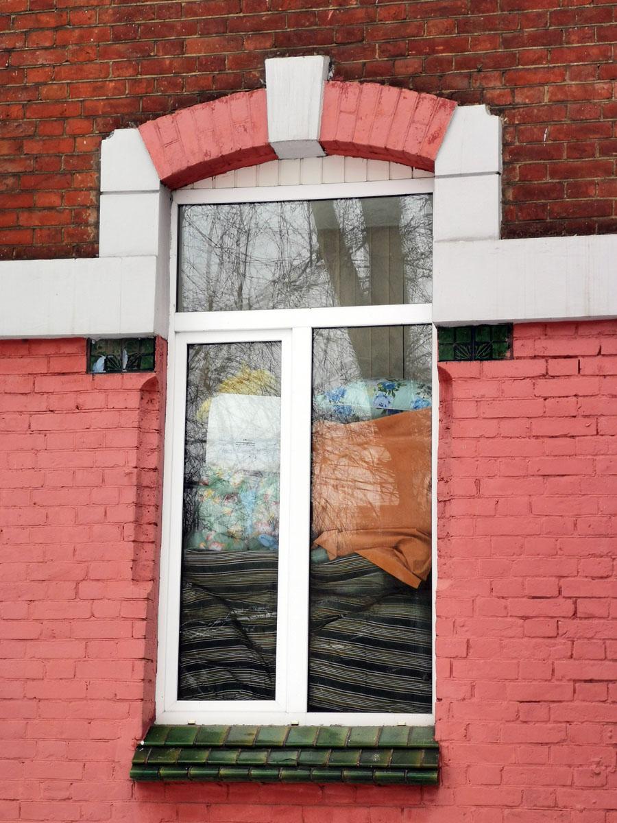 Окна простой формы (по крайней мере сейчас, когда рамы пластиковые) украшены плитками с рисунком по бокам.