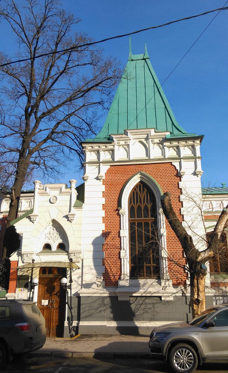 Фасады выполнены в красных тонах с белой отделкой деталей, стрельчатыми окнами, декоративными зубчатыми башенками и теремковой крышей над главным входом.