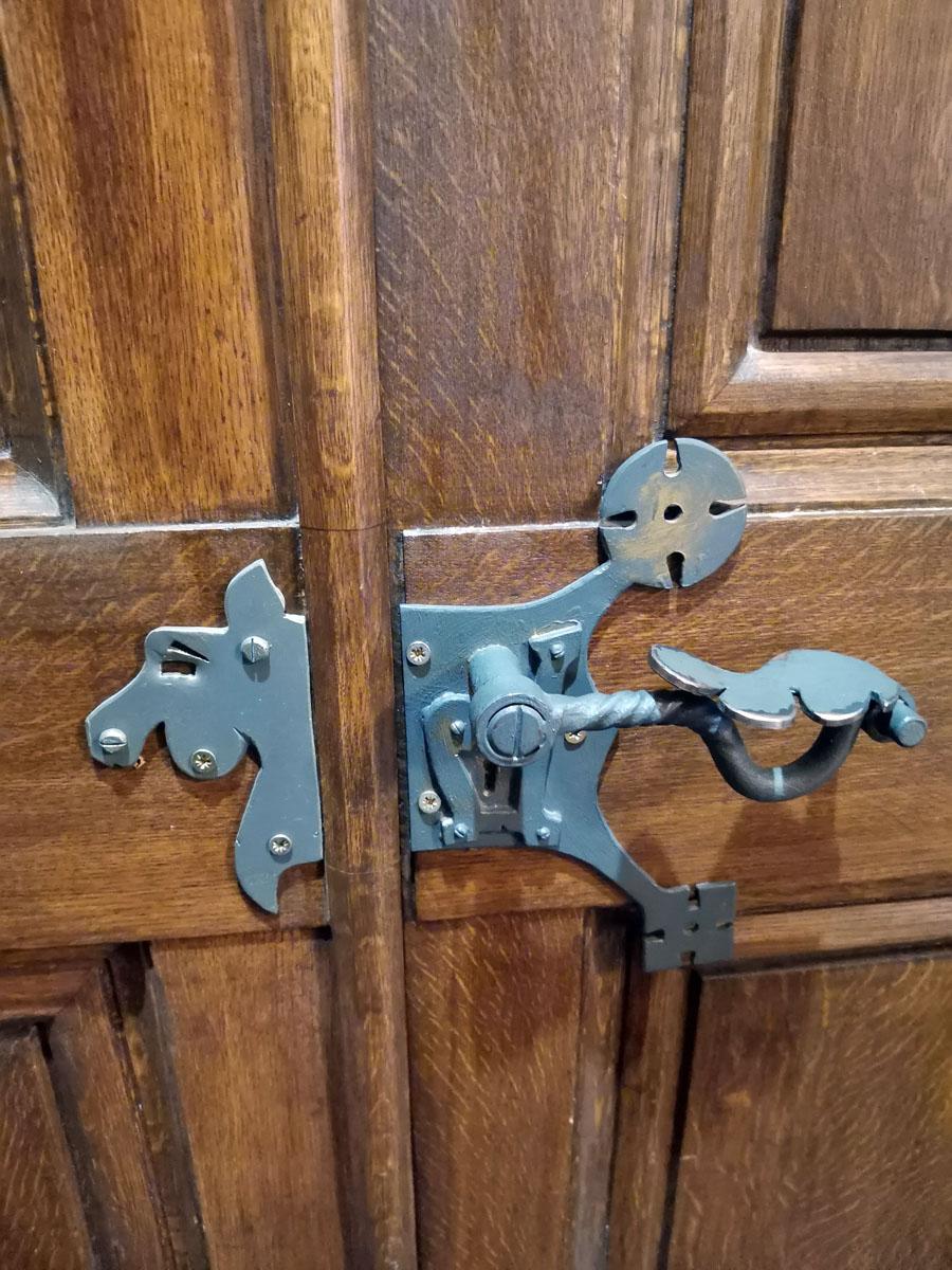При входе в особняк первое, что бросается в глаза, это странные, очень грубо исполненные ручки дверей, которые явно не подходят к этой самой двери. Еще и прикручены одновременно винтами и саморезами с крестообразным шлицем, который изобрели в 1962 году.