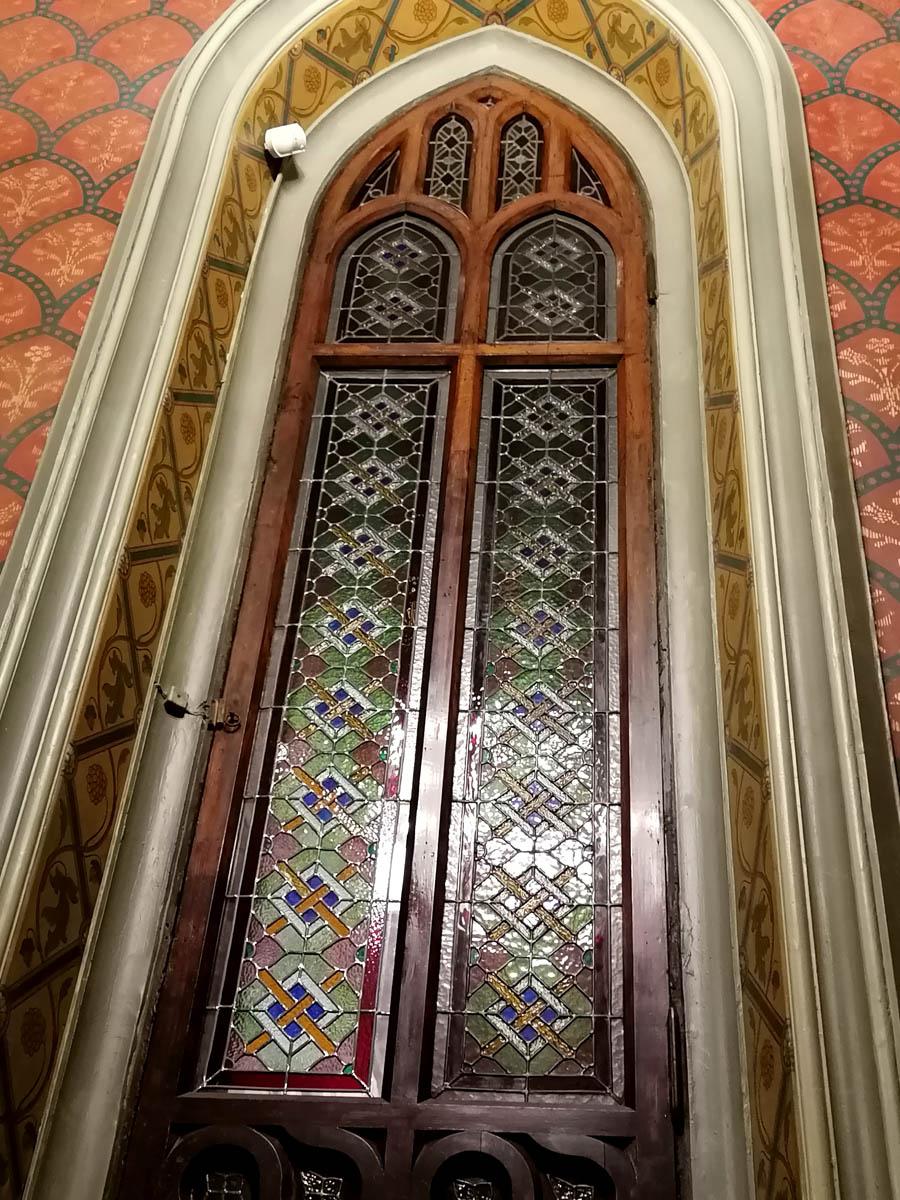 Длинное узкое стрельчатое окно с цветными витражами