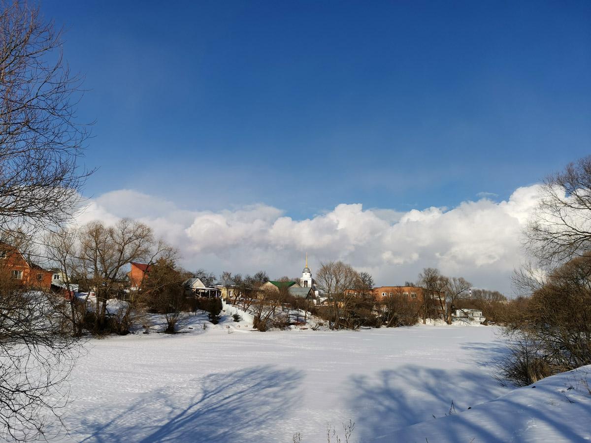 Еще один покрытый льдом и снегом Ивановский пруд, белые облака на фоне синего неба и напоминающая маяк церковь.