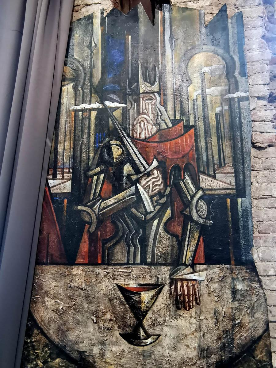 На боковых стенах между окон расположено множество больших стильных картин...