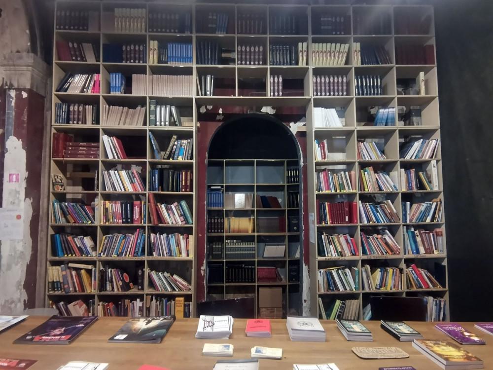 Библиотека церкви. На стеллажах книги. которые можно взять почитать с возвратом. На столе можно забрать навсегда.
