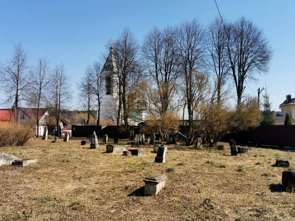 На левом берегу на улице перед территорией храма лужайка с надгробиями. Ранее здесь, действительно было кладбище.
