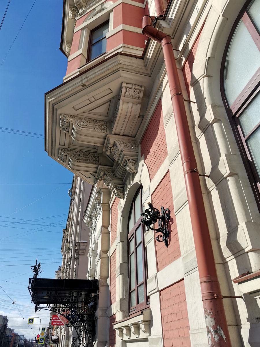 Терракотовый с белой отделкой особняк имеет живописную асимметричную композицию с богатой пластической проработкой фасада.