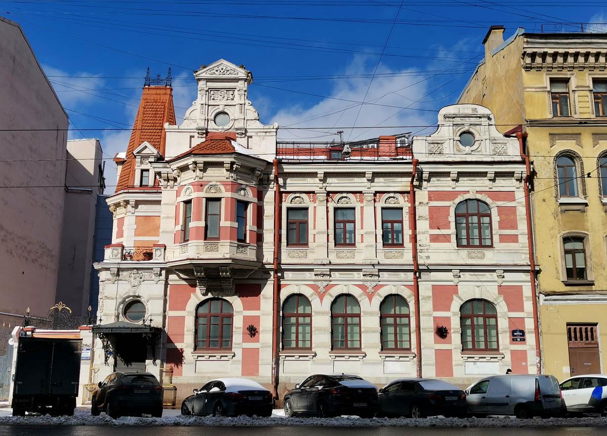 Разные по форме и размерам окна и асимметричный фасад.