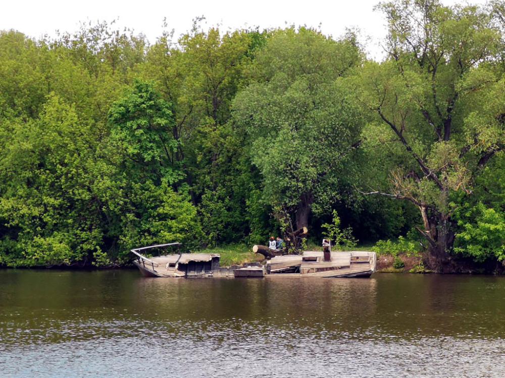 На противоположенном берегу остов заброшенной лодки.