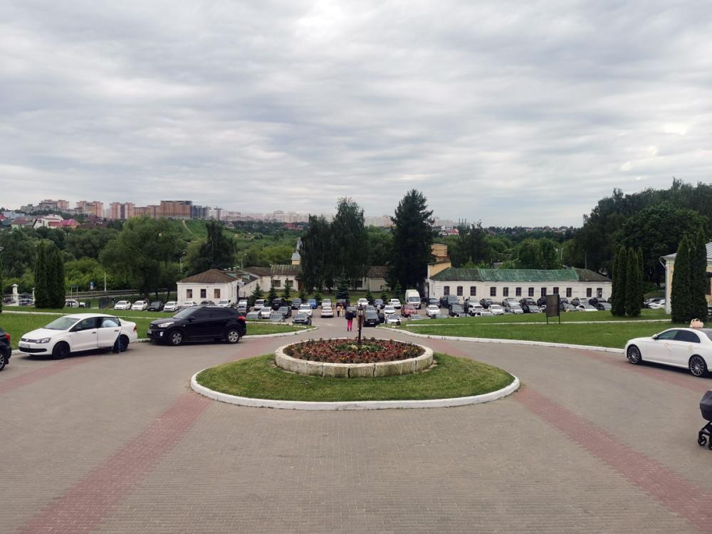 Клумба и спуск к историческому зданию конюшни и парковке.