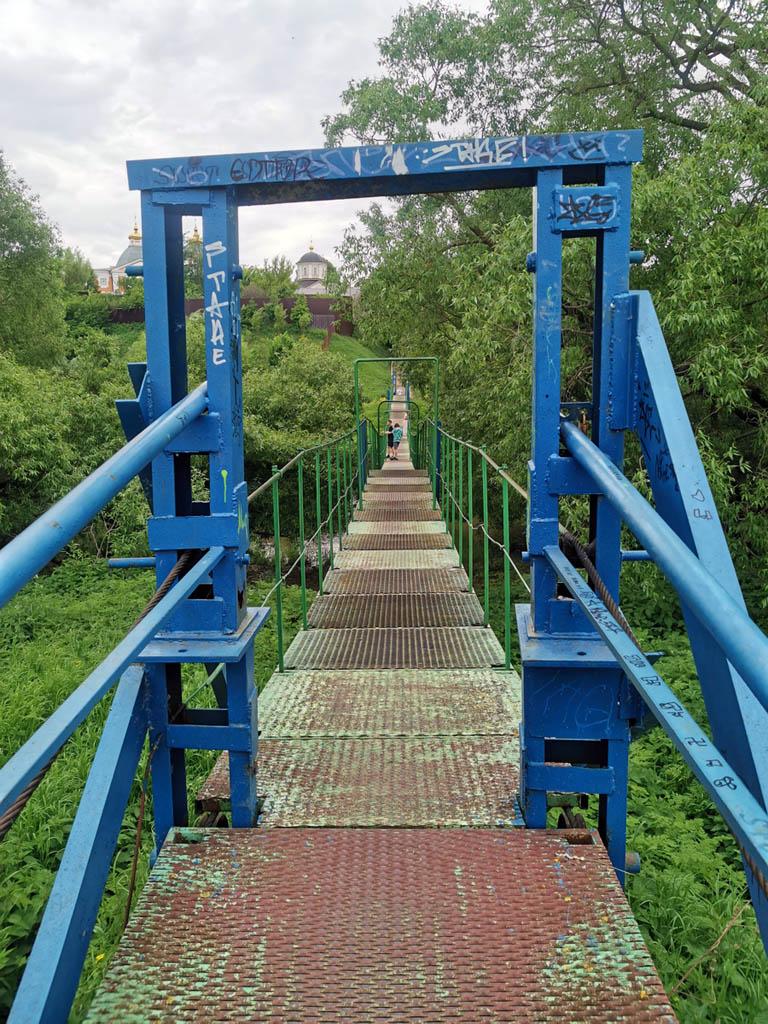 Переходим реку Пахру с левого берега на правый по подвесному пешеходному мосту. На противоположенном берегу виден Храм Илии Пророка в Лемешове.