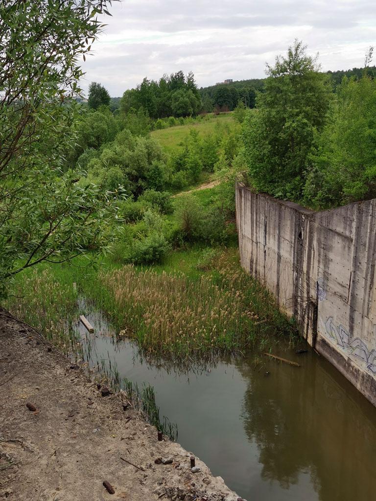 Поднимаемся на земляной вал и подходим к краю бетонной стены.