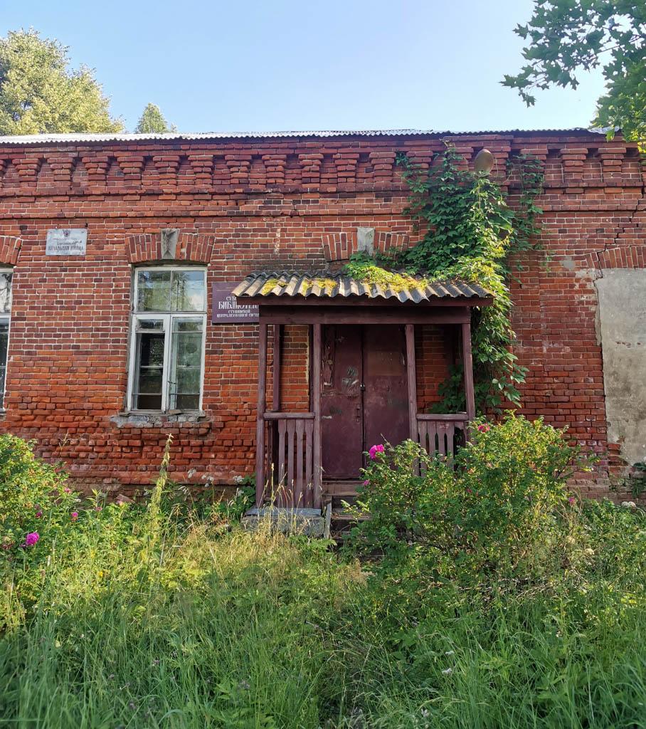 Старинное здание в селе Суково. На стене прибиты таблички, что здесь расположены начальная школа и библиотека. Но разбитое окно и заросшая дорожка к входу наводят на мысль, что данные упреждения уже оптимизировали.