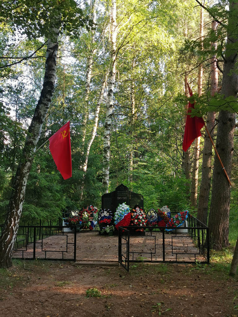 В тени деревьев мемориал посвященный погибшим во время ВОВ жителям села. На деревьях флаги под которыми воевали герои.