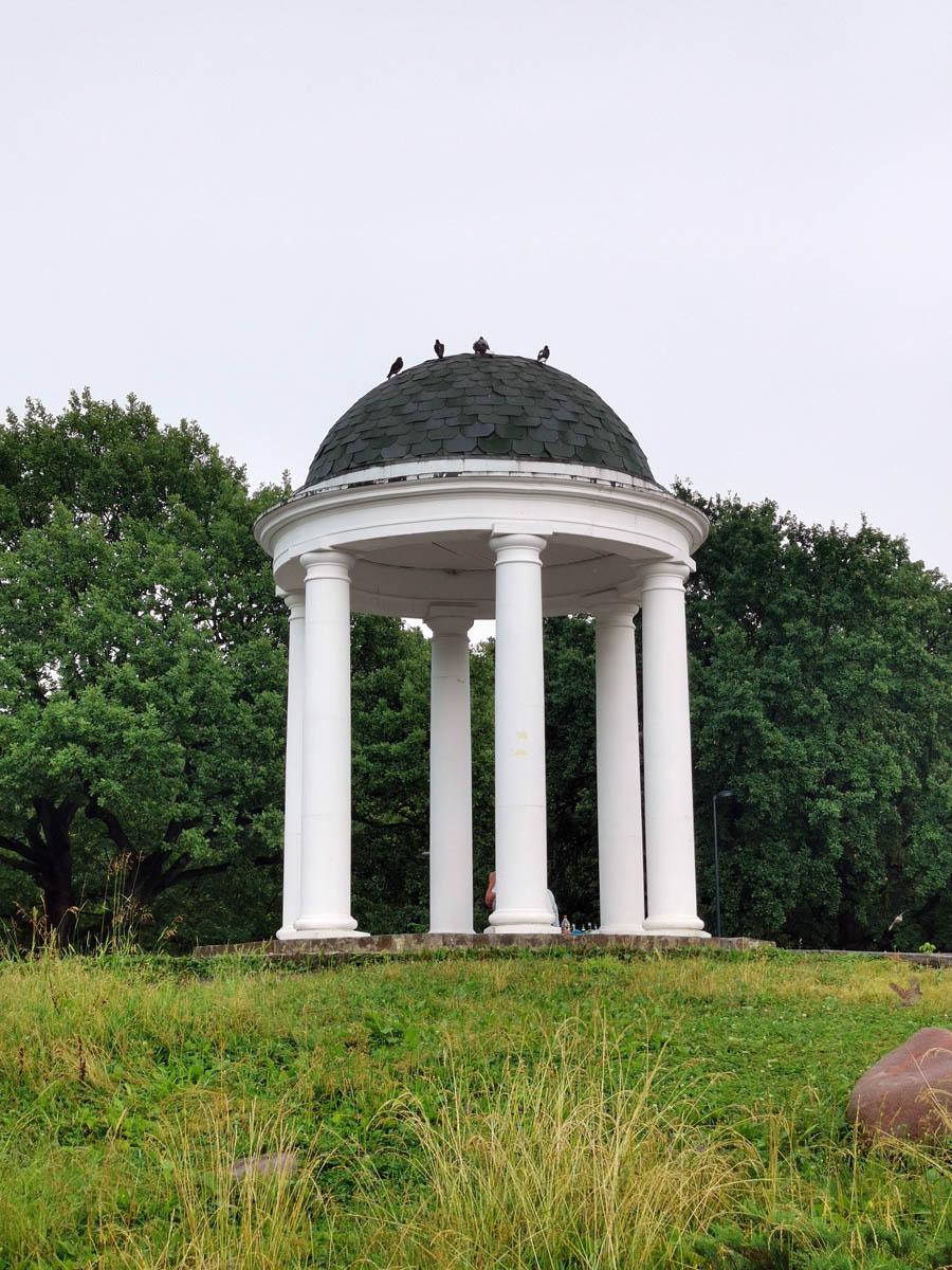 Беседка-ротонда сейчас напоминает классическую. Но изначально на ее месте была конструкция с худыми колоннами и прозрачным куполом из синего поликарбоната. Смотрелось ужасно, тем более, что пластиковая крыша быстро развалилась.