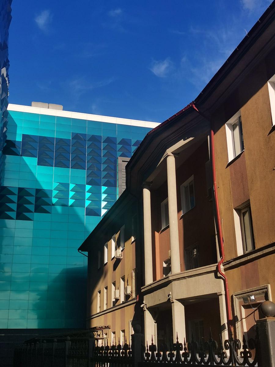 Здание довоенной постройки на фоне современного торгово-развлекательного комплекса.