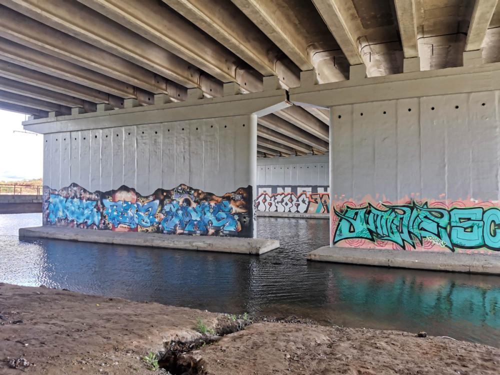 Все опоры моста разрисованы граффити