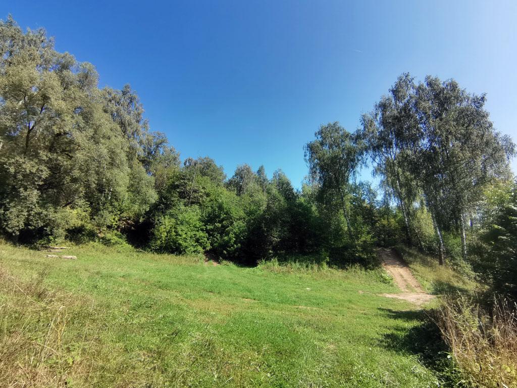Большая поляна ограниченная рекой и высоким крутым берегом со скальными выходами известняка