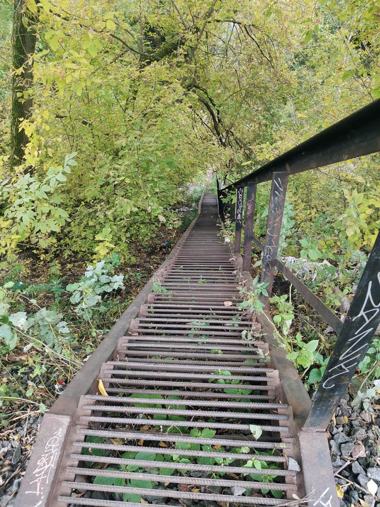 Через небольшое расстояние спускаемся от ЖД-ветки по крутой лестнице в низ в довольно глубокий овраг с дном в виде каменистой площадки в петле речки Котловки