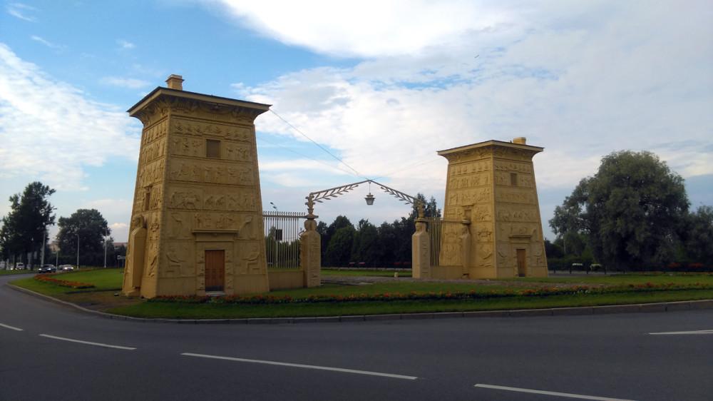"""Египетские ворота построены по проекту архитектора А. А. Менеласа в 1827-1830 годах. Во время Великой Отечественной войны пострадали от артиллерийского огня. Некоторые разбитые осколками снарядов чугунные плиты пришлось отливать заново. В послевоенные годы ворота неоднократно ремонтировались и реставрировались. В 1980-х проезжая часть была перенесена на территорию вокруг ворот. В 1987 году в них врезался грузовик... Ворота отремонтировали, а дорогу """"загнули"""" в обход и сейчас ворота огибают две встречные полосы Петербургского шоссе. Булыжное мощение под сквозной аркой ворот напоминает об историческом облике полотна Царскосельской дороги, которая с 1717 г. направлялась отсюда по прямой перспективе к Екатерининскому дворцу. А вот, подойти к воротам не нарушая правила дорожного движения нельзя, пешеходного перехода не существует."""