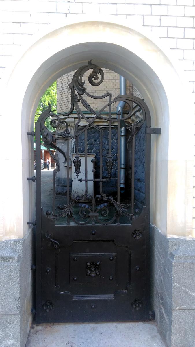 Слева от особняка стильные кованные калитка и ворота. Калитка заперта....