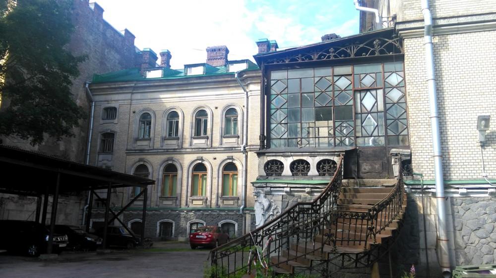 Главный дом вид со двора. Сразу бросается в глаза стеклянная веранда с металлической лестницей.