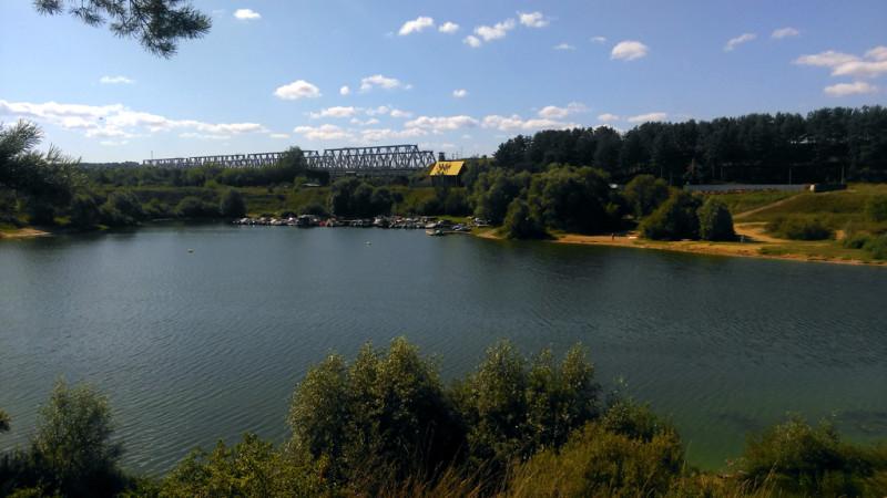 Вдалеке видны Железнодорожные мосты Павелецкого направления Московской железной дороги через реку Оку. А у причала скопление лодок и катеров. Правее, почти пустынный пляж.