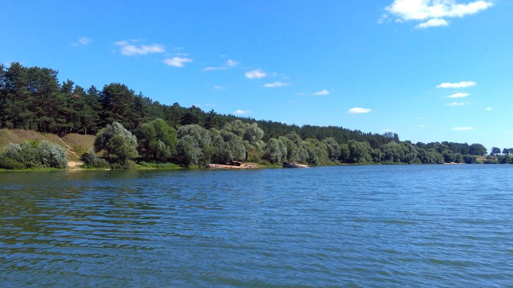 Фото с западного берега, где расположен пологий песчаный пляж и причалы яхт-клуба.