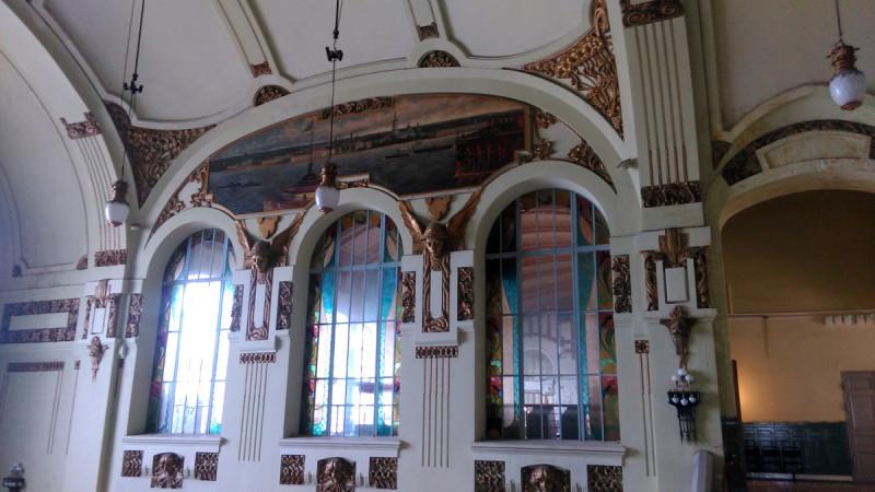 Между окнами в простенках установлены лепные панно, окрашенные под цвет старой бронзы. На них изображения Меркурия и женских головок, декорированных растительным орнаментом. Меркурий - бог торговли и путешествий.