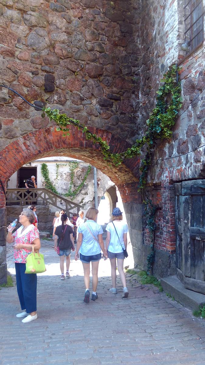 Завершаем осмотр крепости и выходим через арку. Справа дверь в Тюремную башню.