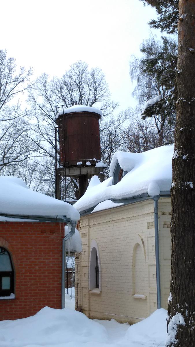 А за корпусами на соседней территории старая водонапорная башня.