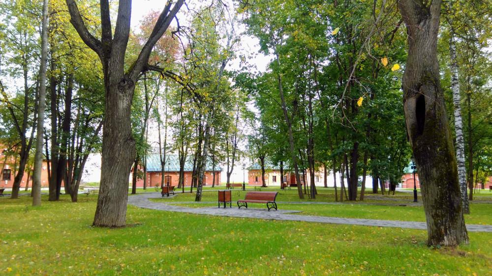 Вид на центральную часть парка. Дорожки, скамеечки, стильные урны, газон. Все чистенько, аккуратненько.