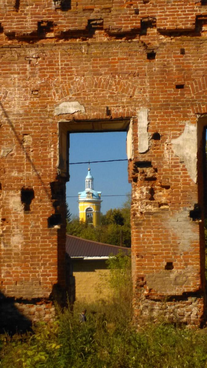 Сквозь проем в стене виднеется колокольня Церкви Покрова Пресвятой Богородицы.