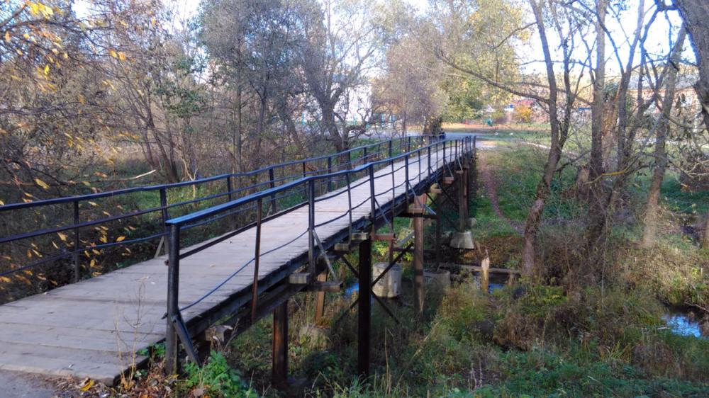 Рядом пешеходный мост через речушку.
