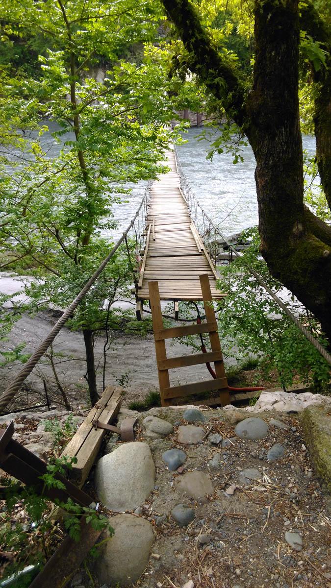 Из Адлера доехали на автобусе до остановки напротив форелевого хозяйства. И пошли к подвесному мосту через реку Мзымта. Первые пару метров моста просто сгнили и обвалились. Но к оставшейся части его прислонили наспех сколоченную лестницу.