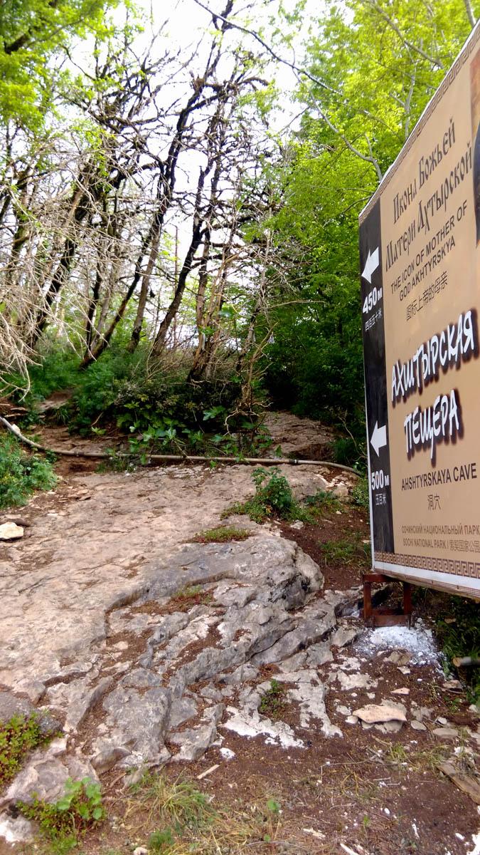 Ну, а мы отправляемся обратно через реку Мзымта к Ахштырской пещере. Баннер на русском, английском и китайском языках указывает нам на неприметную тропинку на склоне горы.