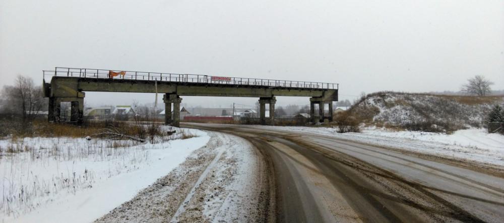 Впереди виден заброшенный железнодорожный путепровод. Насыпь к нему примыкающая с обеих сторон срыта. То ли ради песка, то ли, что бы на мост нельзя было забраться...