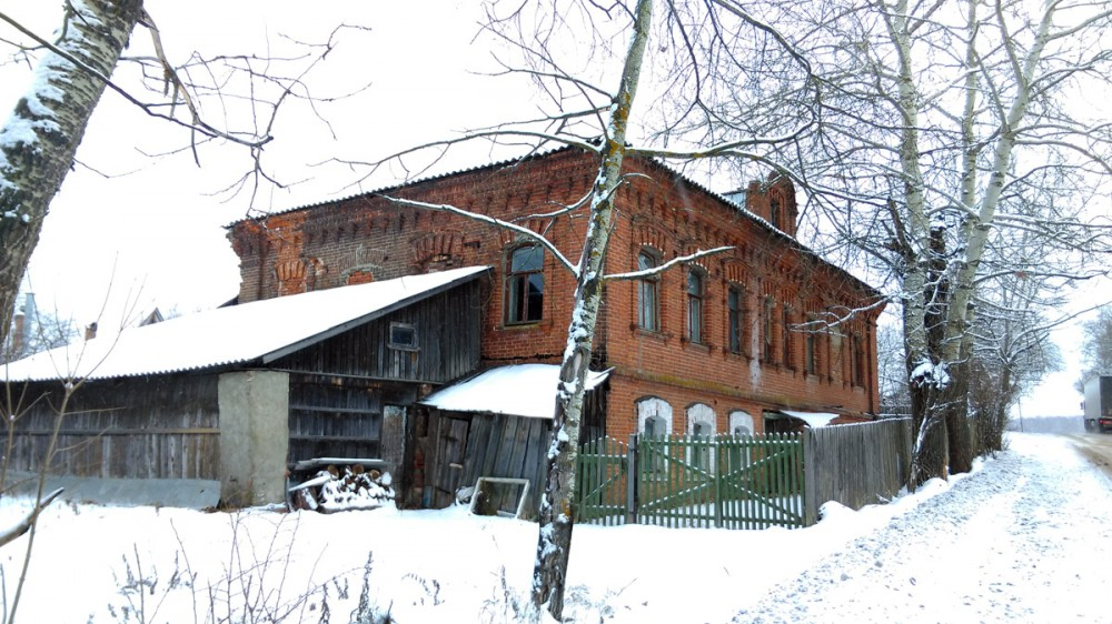 Слева от дороги добротный старинный дом с деревянными более поздними пристройками.