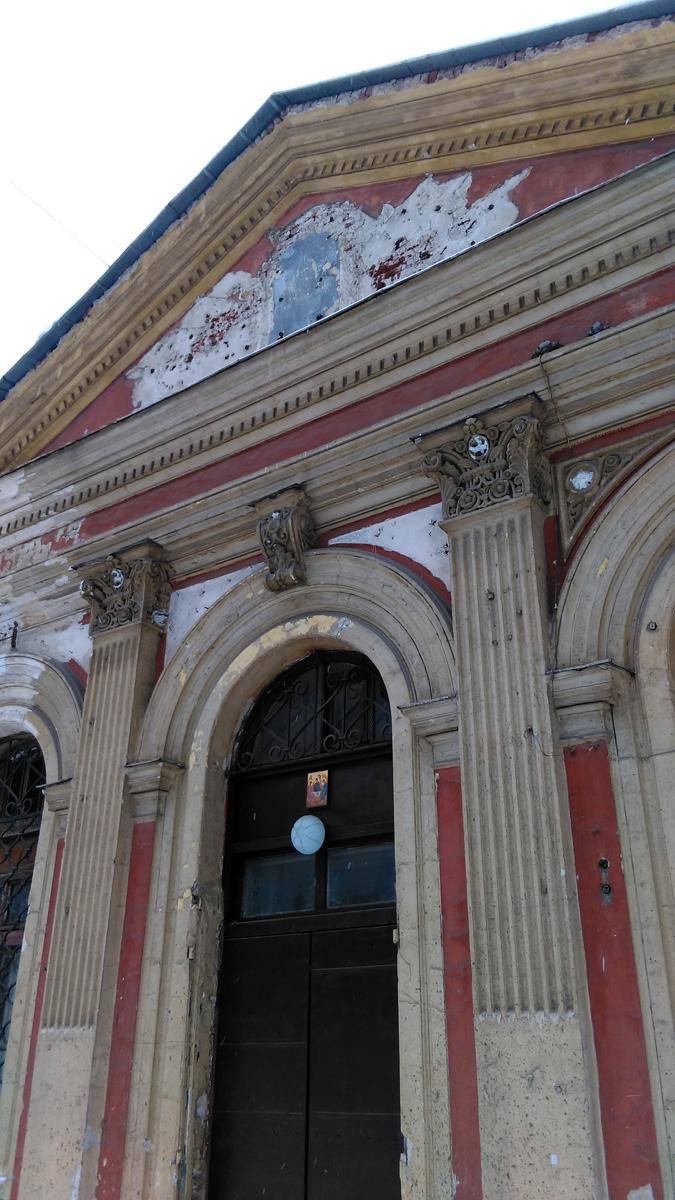 На фронтоне угадываются силуэты знамен. Здесь действительно были герб и знамена, когда храм перестроили в клуб (тир) ворошиловских стрелков.