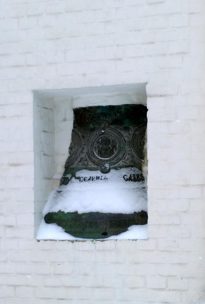 В стену колокольни вмонтирован обломок старинного колокола