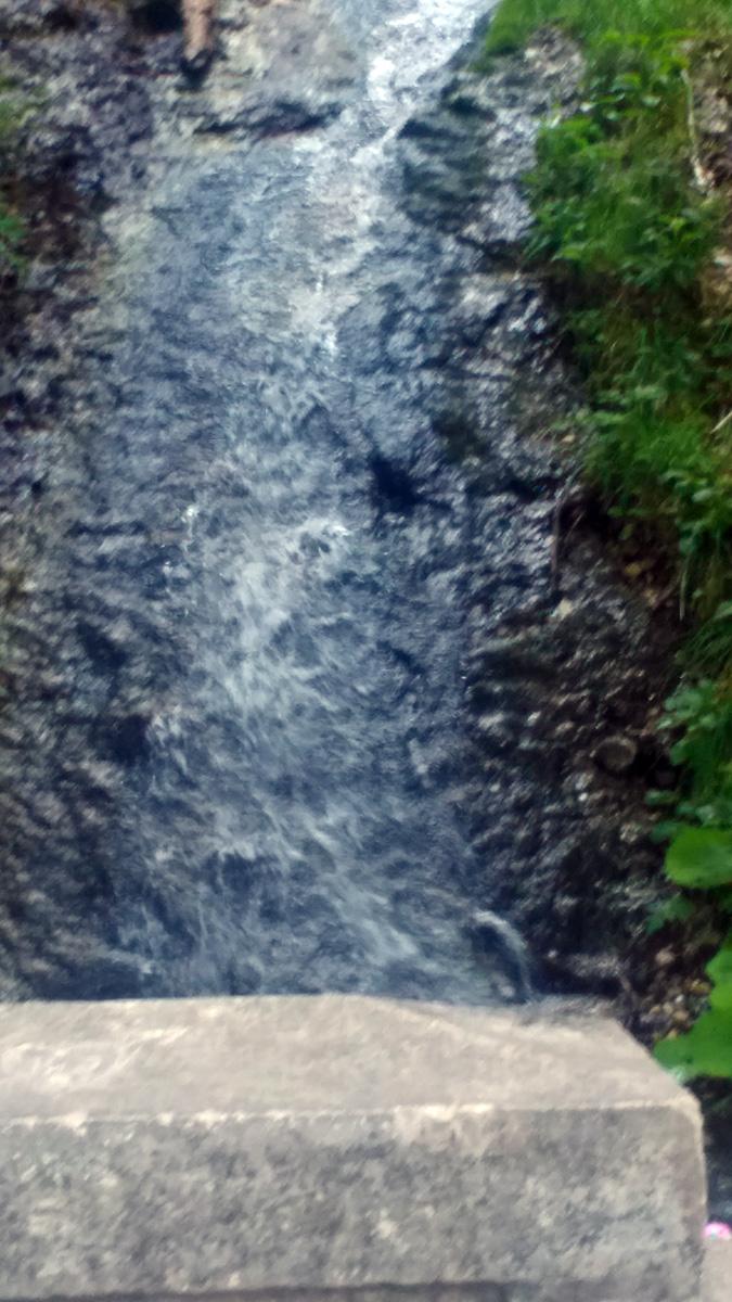 Сверху по склону бежит ручеек и ныряет в трубу под дорогой