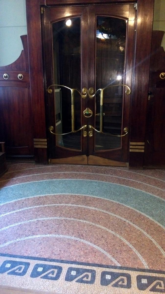 Двустворчатые двери главного входа. Не смотря на возраст и то, что раньше не было технологии закаливания стекла, стекла целые и настоящие. Благодаря, прежде всего, конструкции дверных ручек, которые помимо основной функции еще и защищали стекло.
