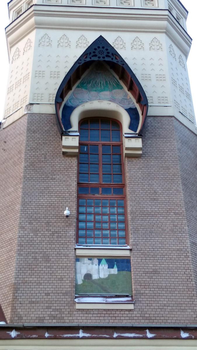 Под окном керамическое панно со средневековой крепостью