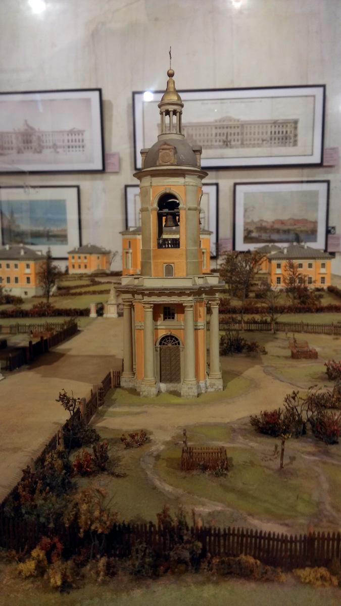 Колокольня и сейчас функционирует. А справа к ней пристроен  в 1858 году Храм Покрова Пресвятой Богородицы. Но на макете показан более ранний период.